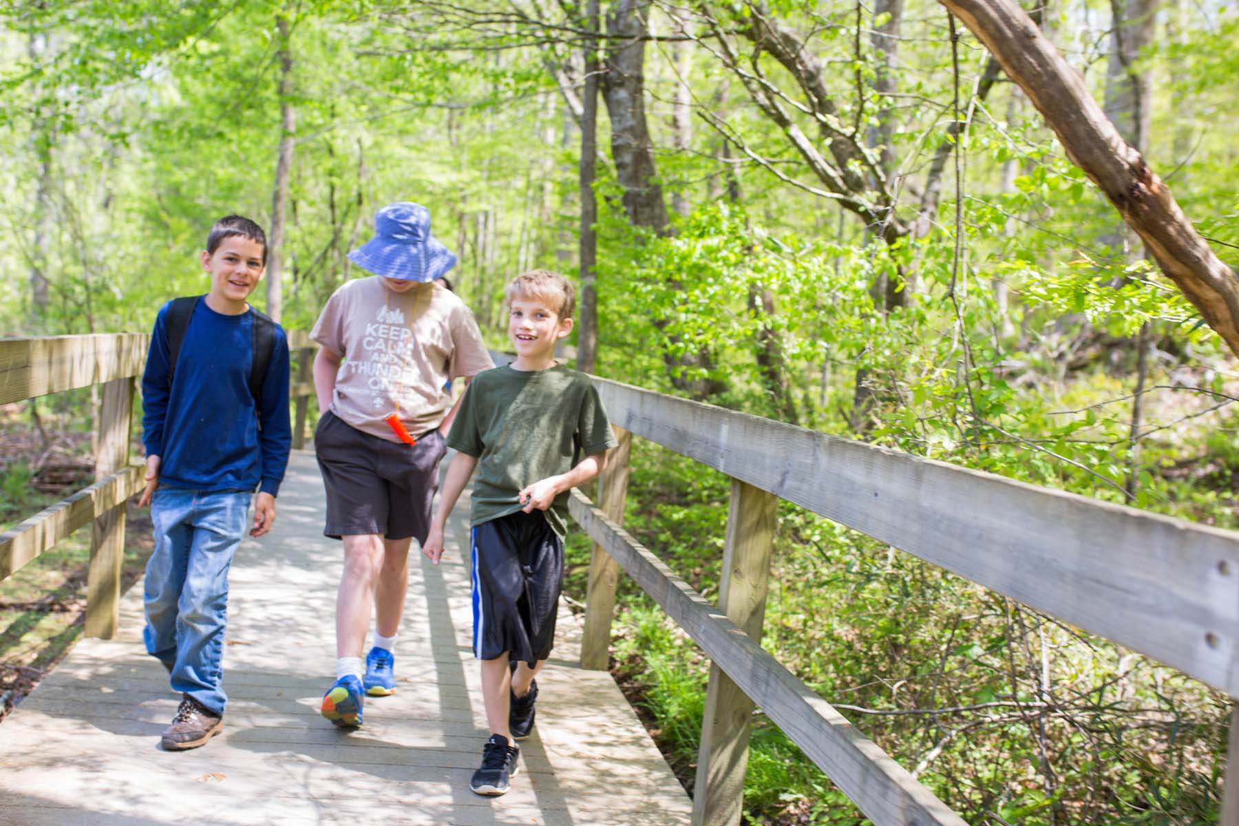 Three boys walk down the boardwalk. They are about 10 to 12 in age. One wears a navy blue shirt and jeans. One wears a khaki shirt, dark shorts, and a denim bucket hat. The third wears dark shorts and an olive green shirt. They are surrounded in green trees and vegetation. They are smiling.