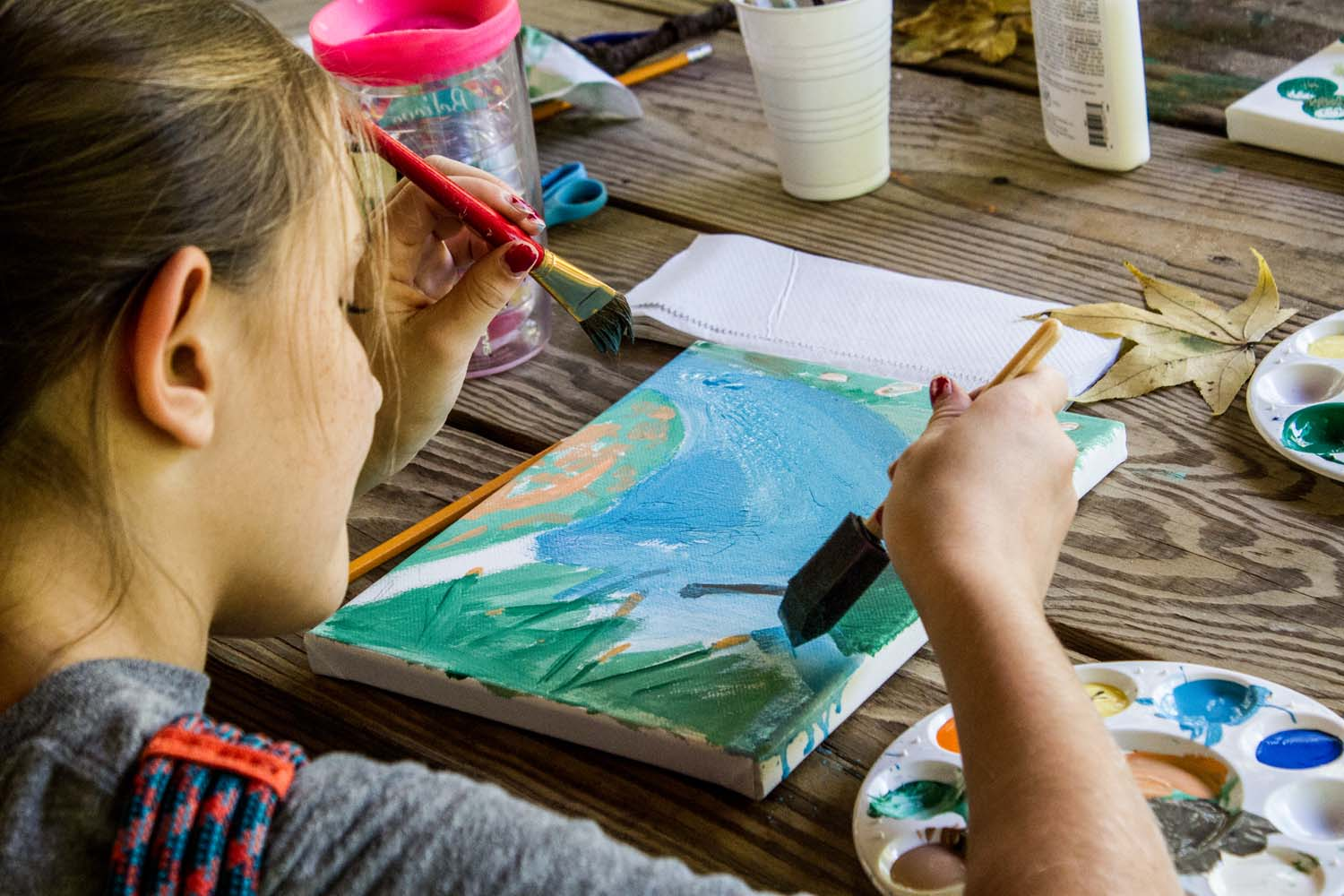 The photo is taken from behind a girl painting. She holds a sponge as she paints a wetland scene of cattails and blue sky. Upon the table are paint palettes with a variety of colors, a water cup for paint brushes, a cup of drinking water, glue, scissors, and paper towels. The table is wooden.
