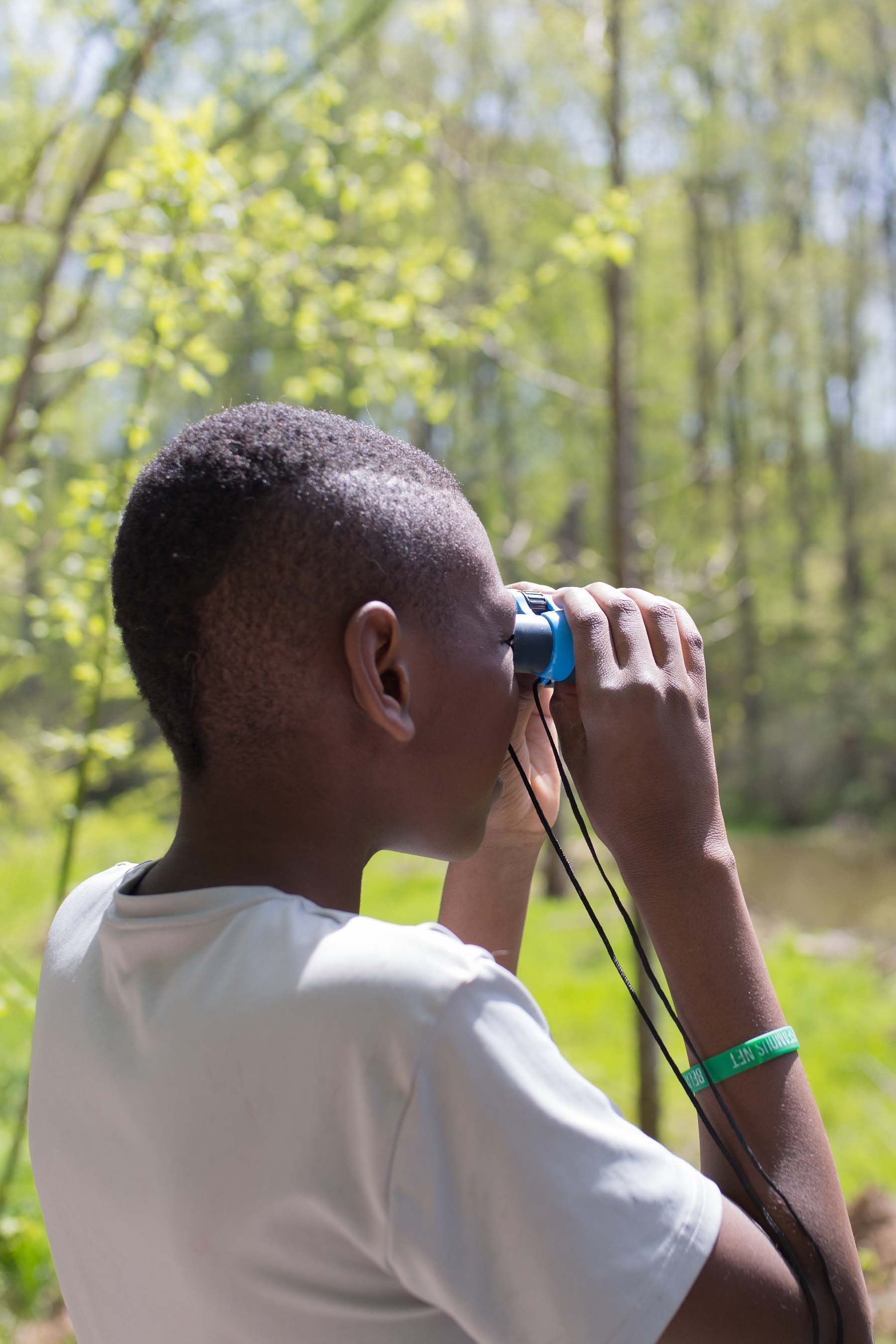 A boy with a faux hawk looks through binoculars. he wears a white t-shirt and is surrounded by green vegetation and trees. He is looking to the right and away from the camera.