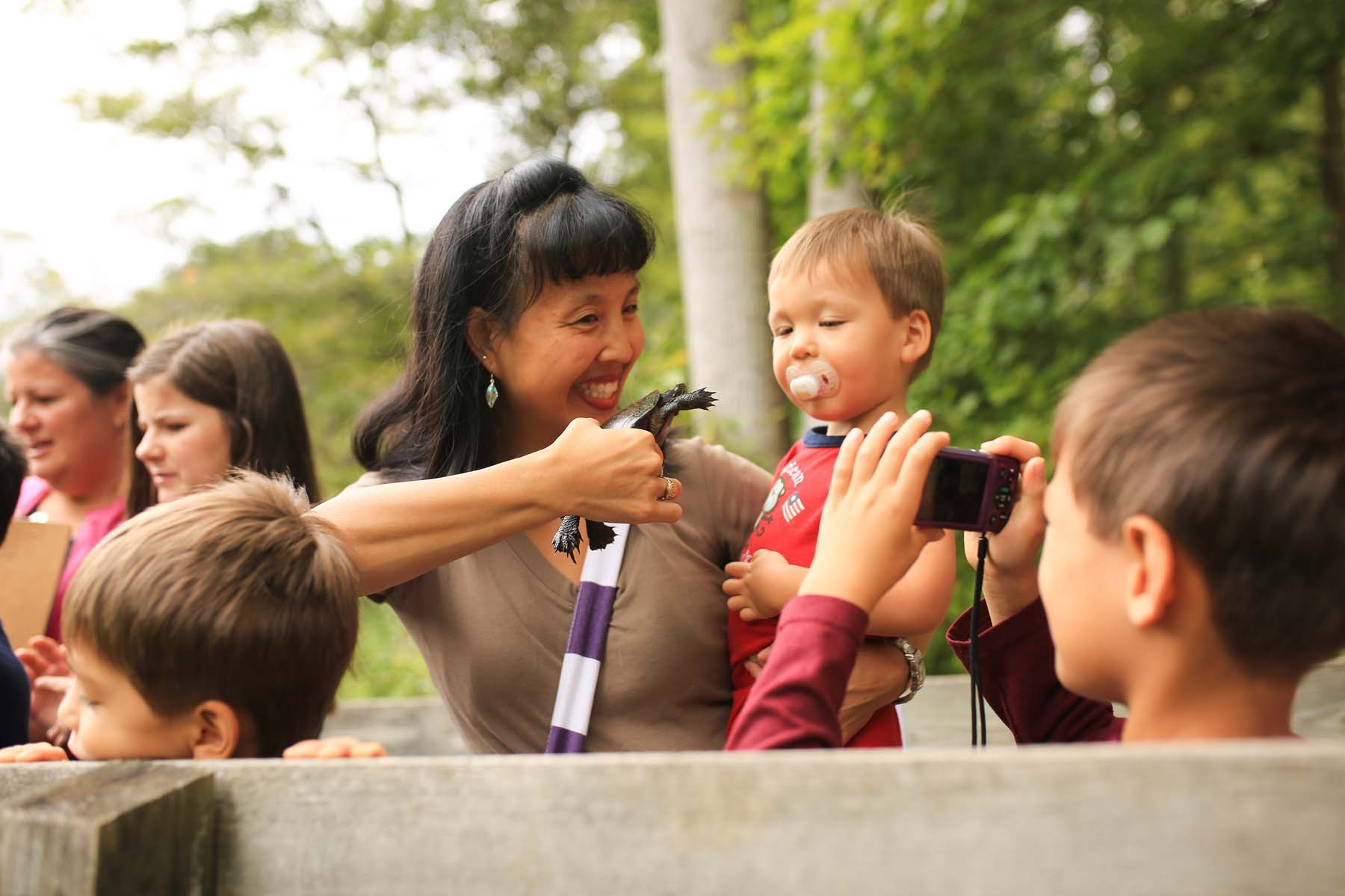 A woman introduces her toddler son to a turtle. She is smiling and her son is smiling behind his pacifier. Another of her sons photographs the scene with a cell phone. There are trees in the background and a boardwalk rail in the foreground.